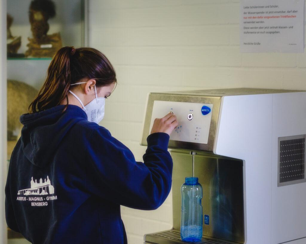 Schülerin nutzt Wasserspender