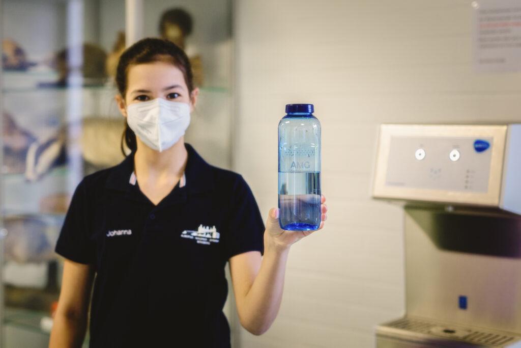 Schülerin zeigt frisch gefüllte Wasserflasche